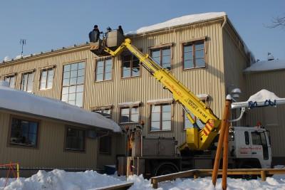 Med hjälp av lyftkran knackas isen vid takkanterna bort