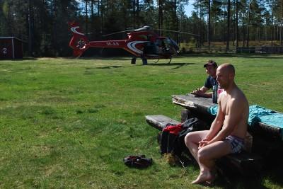 Piloten Tore Schultzberg njöt av det vackra badet och årets premiärdopp vid Skidtjärn. I bakgrunden  helikoptern.