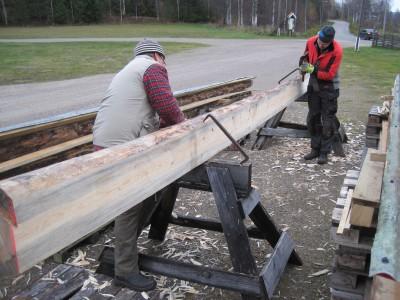 Här skrähuggs timmer som ska ersätta ruttna stockar i linskäkten vid Grissjöbäcken. Urban Larsson och Lars Sahlin håller i yxorna. Foto: Ragnar Jonsson