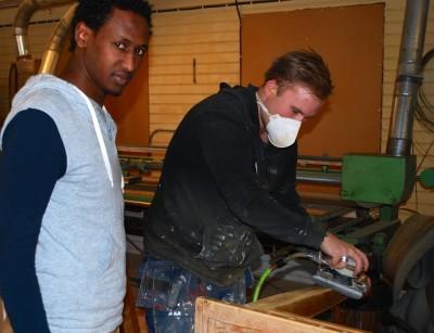 Medhane från Eritrea är möbelsnickaren som nu kanske får praktik i GlösBolagrets snickeri. Här instrueras han av Henrik Ronström med slipmaskinen.