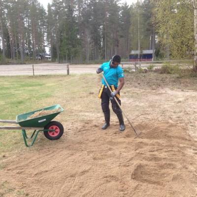 Aschalew Mekuria krattar volleybollplanen som får en ny grusbädd.